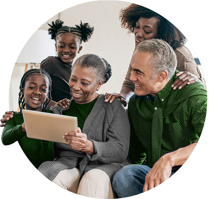 A smiling family looking at a tablet